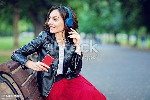 Happy girl is listening music in the park