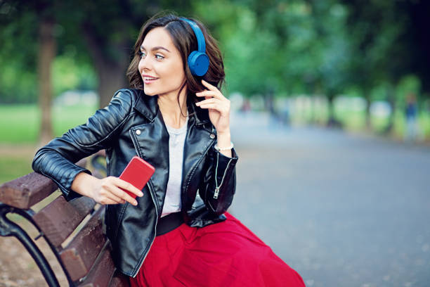 Happy girl is listening music in the park stock photo