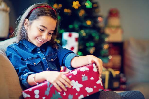 glückliches mädchen öffnet ihr weihnachtsgeschenk - kinder verpackung stock-fotos und bilder