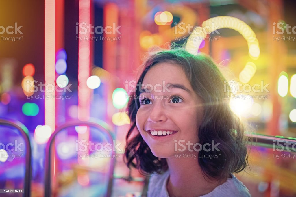 Happy girl is smiling on ferris wheel in an amusement park stock photo