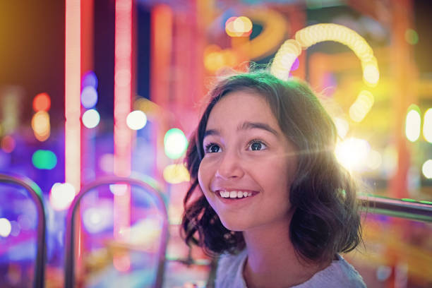 Happy girl is smiling on ferris wheel in an amusement park Happy girl is smiling on ferris wheel in an amusement park traveling carnival stock pictures, royalty-free photos & images
