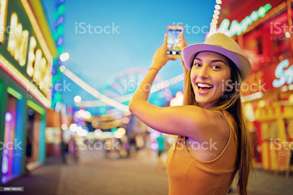 Happy girl is taking pictures with her mobile phone in a funfair stock photo