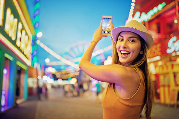 happy girl is taking pictures with her mobile phone in a funfair - game of life stock photos and pictures