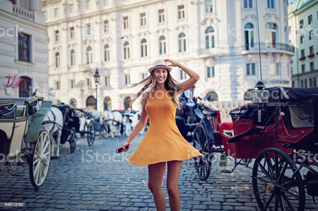 Happy girl is walking and dancing on the street stock photo