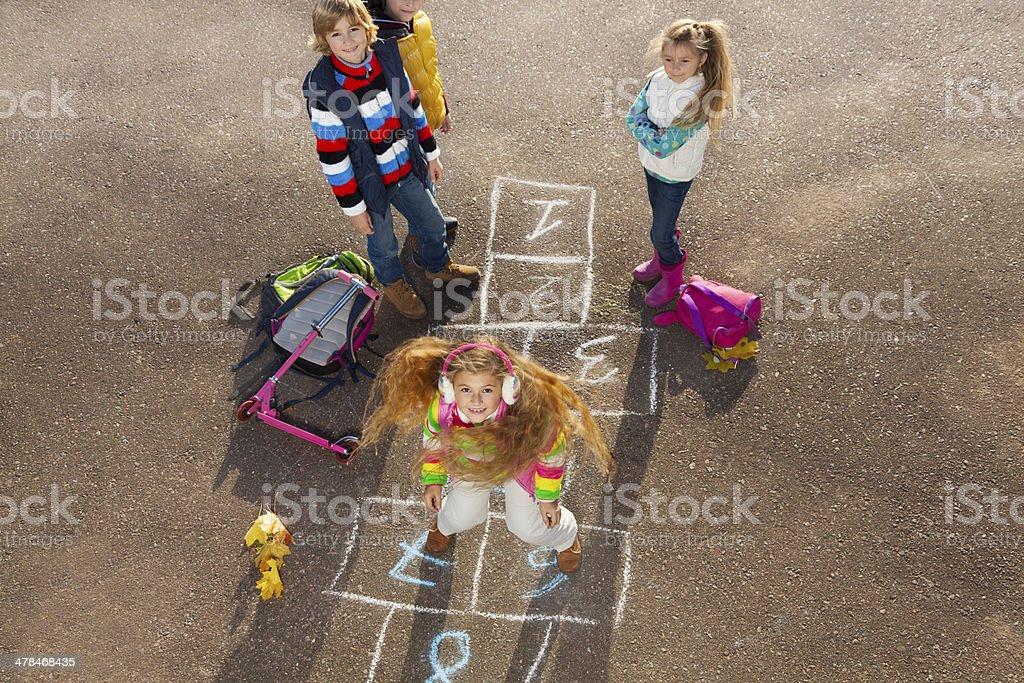 Happy girl jump hopscotch stock photo