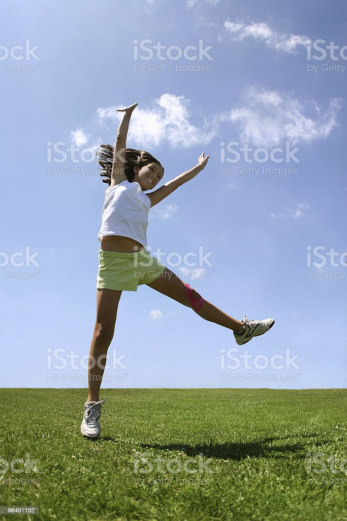 Happy girl jumping around on the grass on a sunny day - Royalty-free Agricultural Field Stock Photo