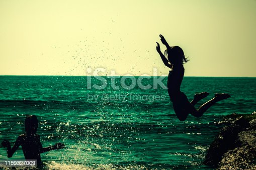 Happy young  girl jumping into the sea.