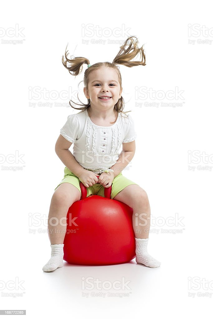 Happy girl jumping on red bouncing ball stock photo