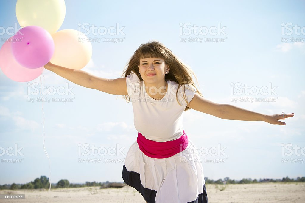 Happy girl jumping with colored balloons royalty-free stock photo