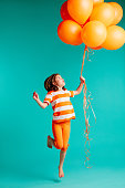 Happy girl jumping with orange balloons in hand. Full length of cute girl child with bunch of helium balloons on blue background.