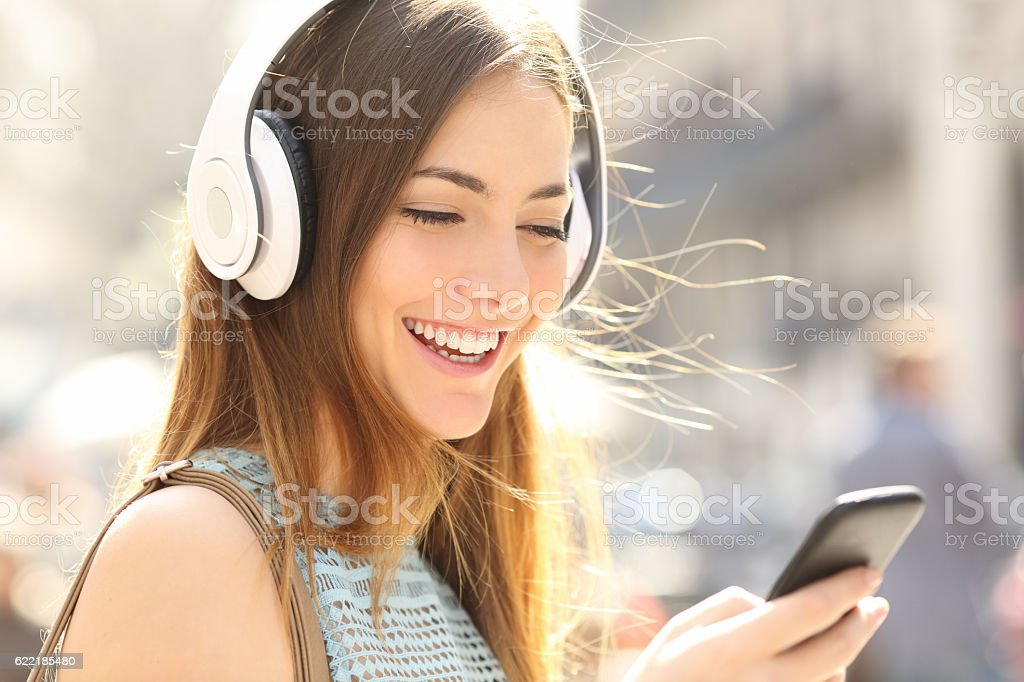 Happy girl listening music with headphones stock photo