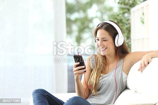 istock Happy girl listening to music from mobile phone 504377090