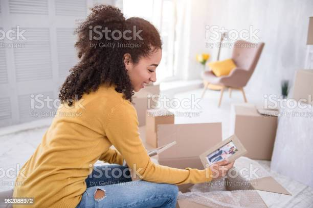 Happy girl looking at photo and smiling while packing picture id962088972?b=1&k=6&m=962088972&s=612x612&h=dk umx5lbdmui7p9pxw1oa2cu5yonyo7rpbk1cdqhf8=