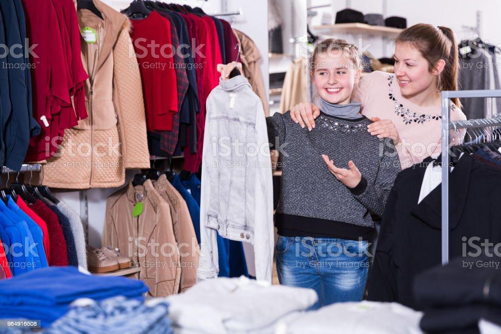 和媽媽一起找衣服的快樂女孩 - 免版稅一起圖庫照片