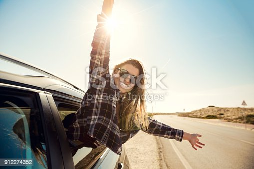 istock happy girl looking out the car window 912274352