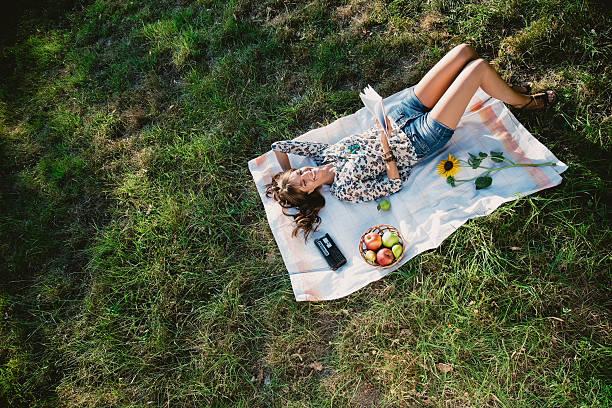Feliz niña caer y leer en un parque - foto de stock