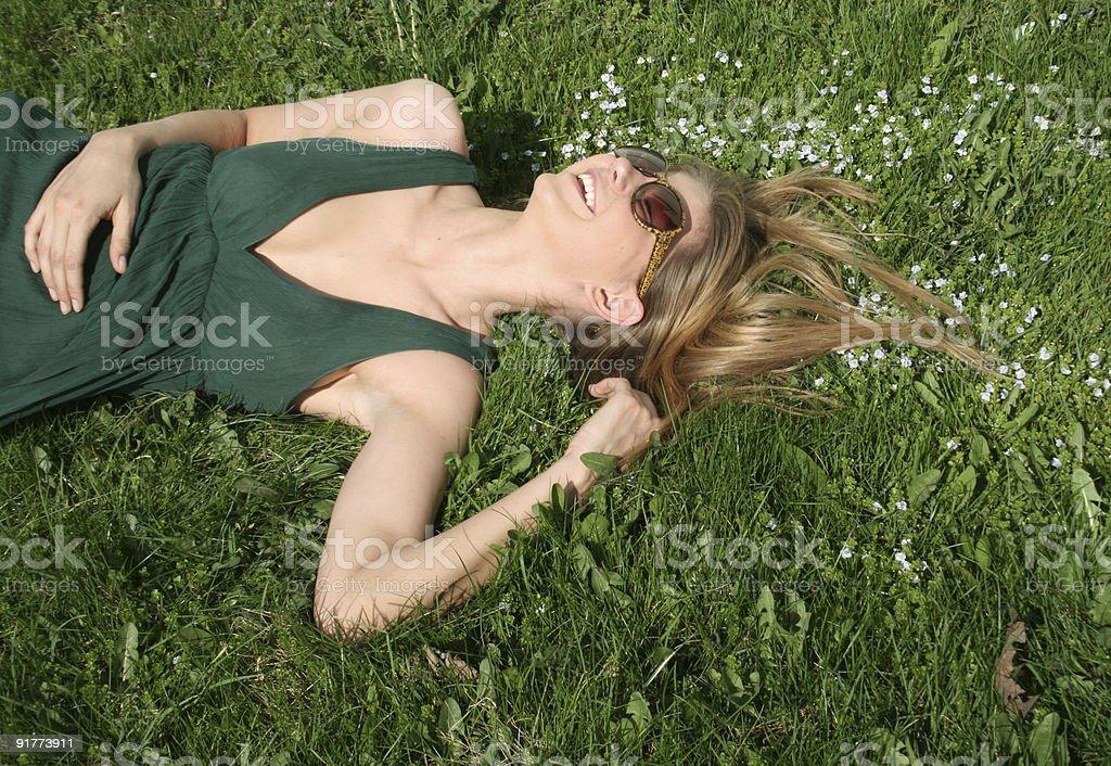 Happy girl lying on grass royalty free stockfoto