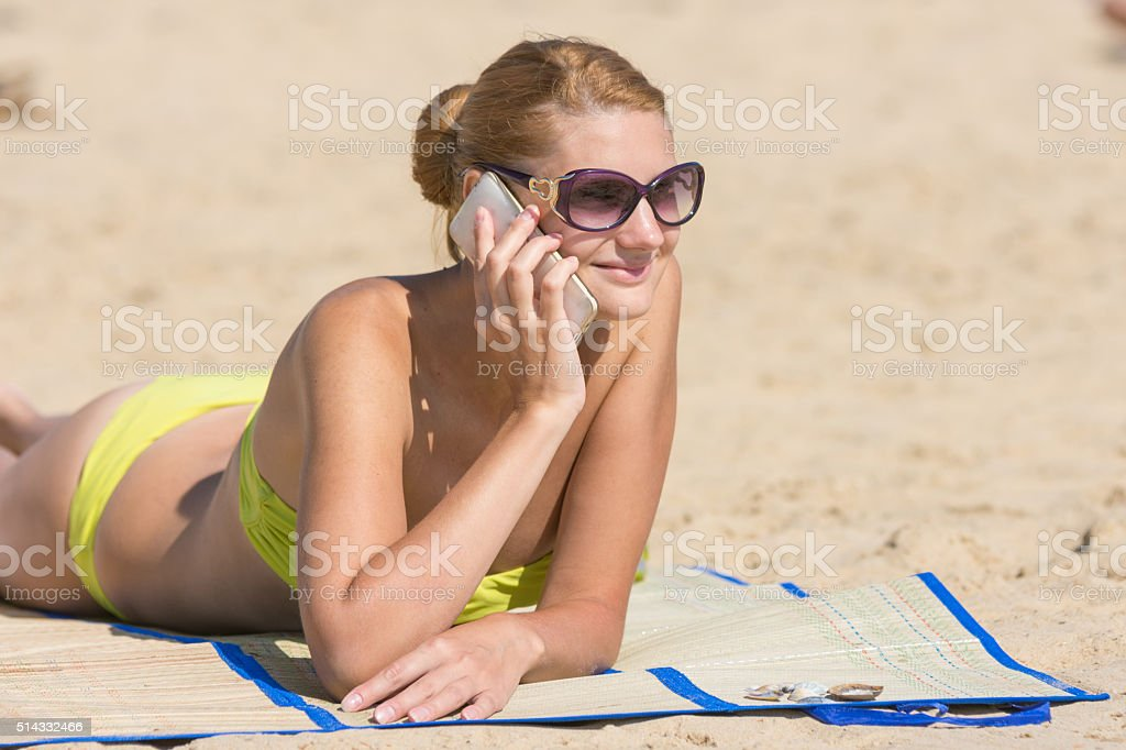 Happy girl lying on the beach and talking on phone stock photo