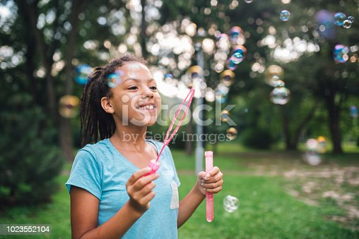 Smiling young girl having fun with bubble wand when making soap bubbles outdoors