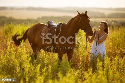 1128475475 istock photo Happy girl near to a horse 506688127
