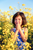 Happy girl on a field of yellow flowers at sunset
