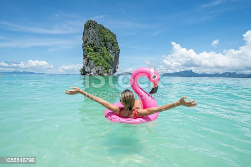 Young woman arms outstretched on idyllic beach with inflatable flamingo playing in pristine clear water in the Islands of Thailand. People travel luxury fun and cool attitude concept