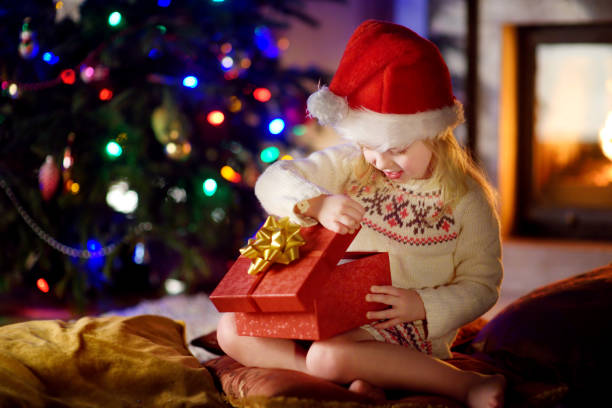Happy girl opening Christmas gifts by a fireplace stock photo