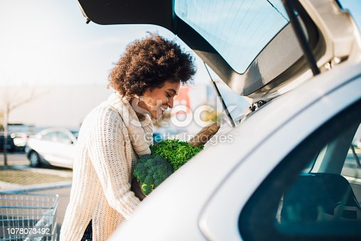 Young woman putting groceries at the car trunk