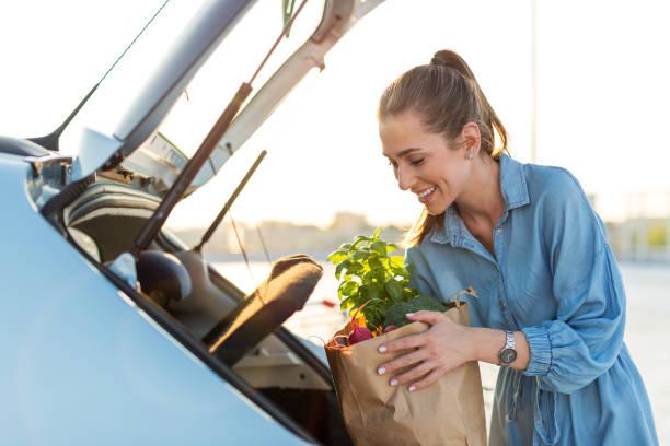 happy girl packing groceries - caricare attività foto e immagini stock