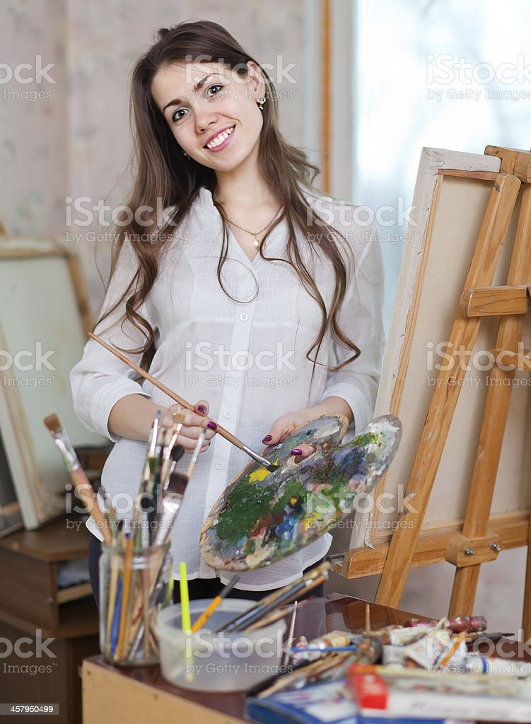 Happy girl paints on canvas with oil colors royalty-free stock photo