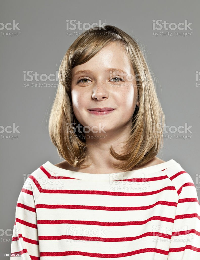 Happy girl Portrait of beautiful girl wearing striped blouse smiling at camera, Studio shot, grey background. 10-11 Years Stock Photo