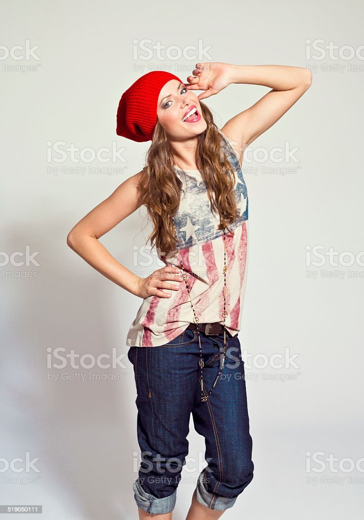Happy Girl Portrait of happy young woman wearing rock style clothes and cap, laughing at the camera. Studio shot, white background. 20-24 Years Stock Photo