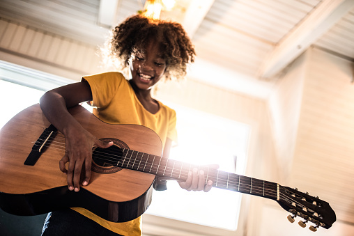 Low angle photo of African American girl playing a guitar at home.