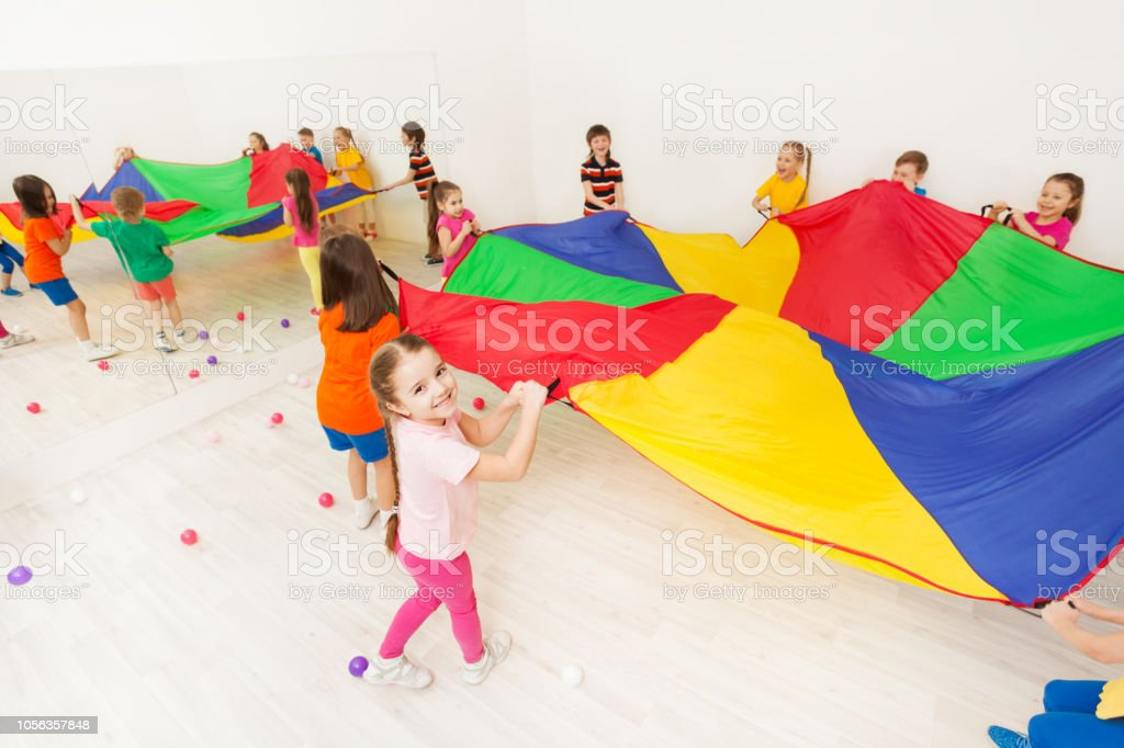 Happy girl playing parachute game with her friends stock photo