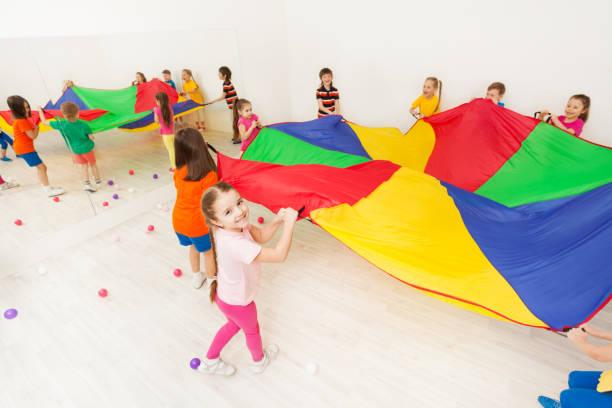Glückliches Mädchen Fallschirm Spiel mit ihren Freunden zu spielen – Foto