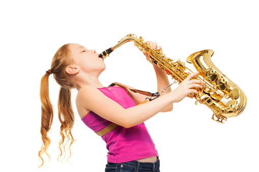 Happy girl playing alto saxophone on the white background