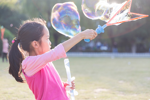 Happy Girl Playing Soap Bubbles In Park Stock Photo
