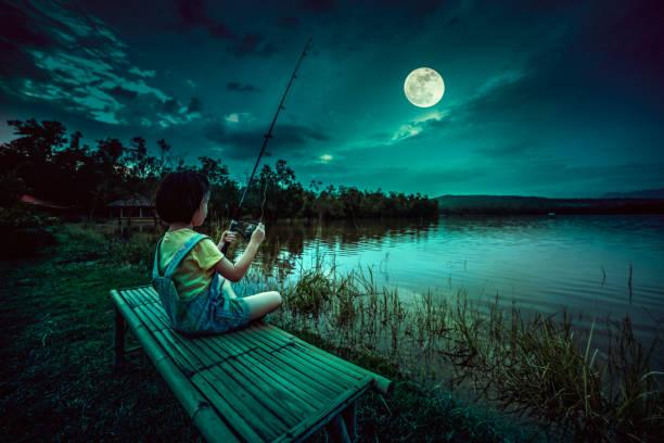 Happy girl pulling rod while fishing against landscape of lake. stock photo