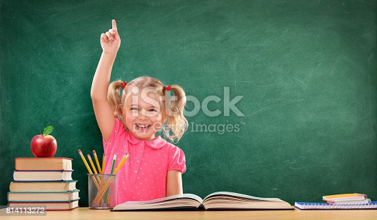 istock Happy Girl Raising Hand In The Classroom 814113272
