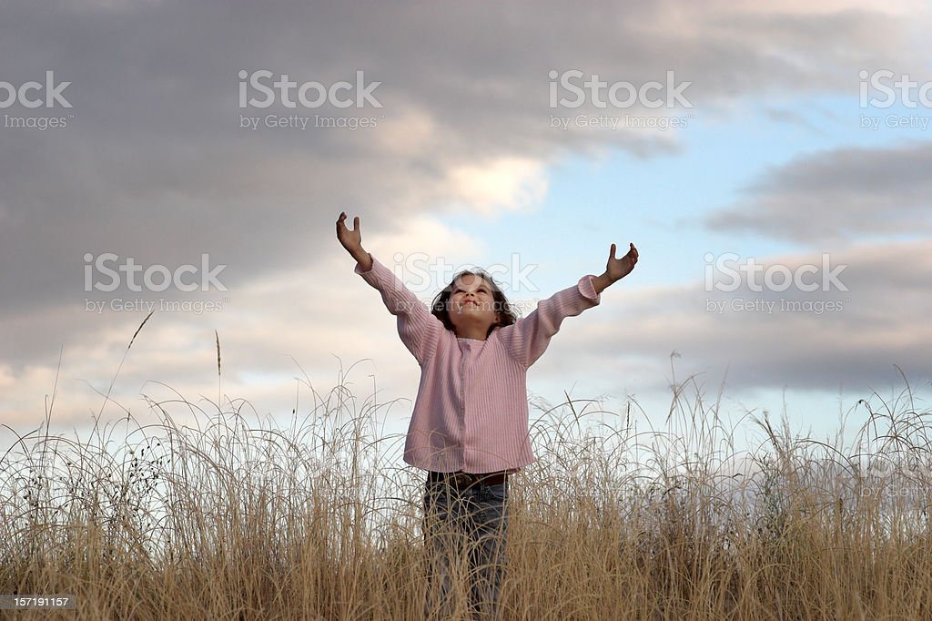 Happy Girl Reaching for Sky and Looking Up stock photo