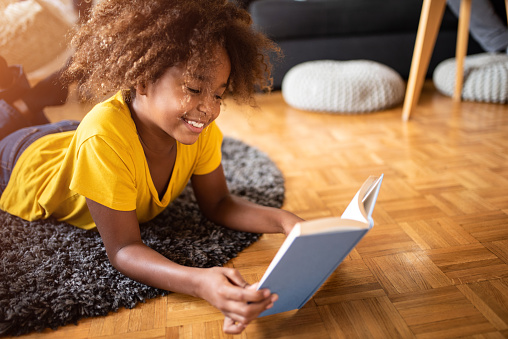 African American girl relaxing on living room floor and reading a book. Learning for school, being creative.