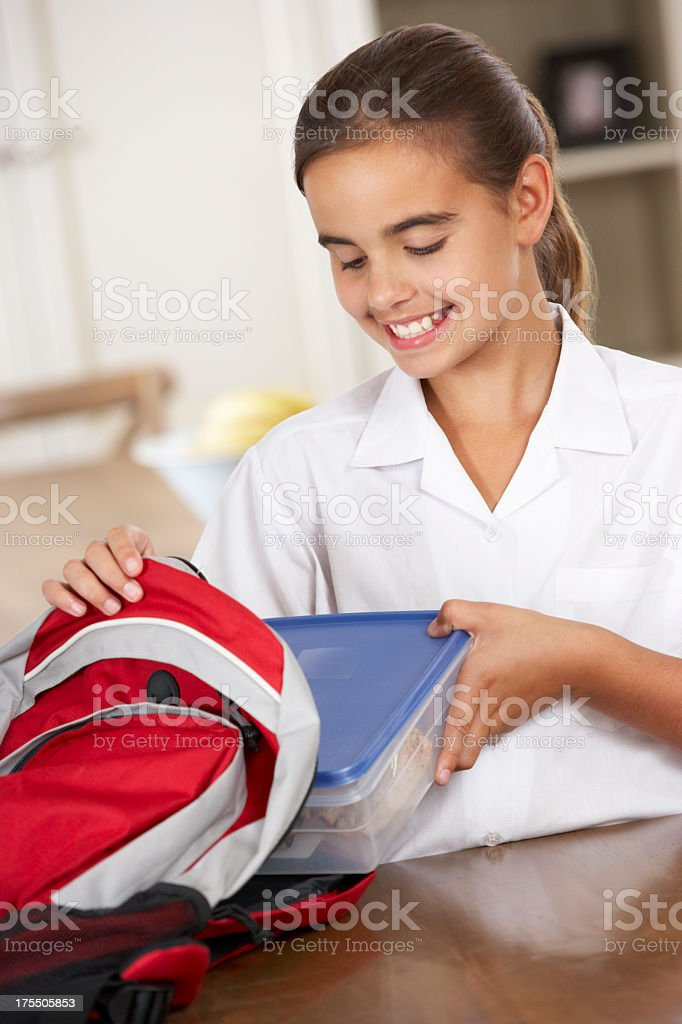 Happy girl ready for school putting lunchbox in her backpack royalty-free stock photo