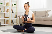 istock Happy girl refreshing with water and using phone after training 1179532771