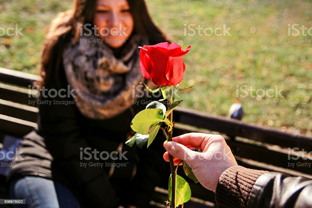 Happy girl relaxed in the park looking at red rose - foto de acervo