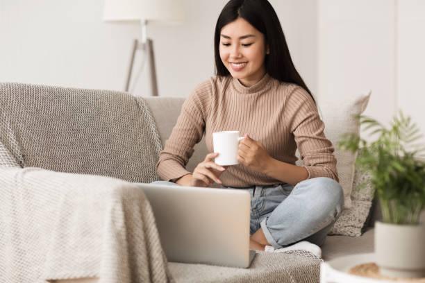 chica feliz relajante en cómodo sofá y el uso de la computadora portátil - café bebida fotografías e imágenes de stock