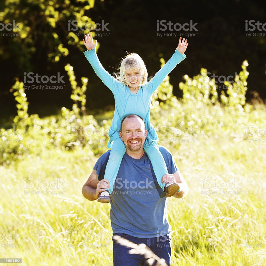 Happy girl riding on smiling dad's shoulders in meadow stock photo