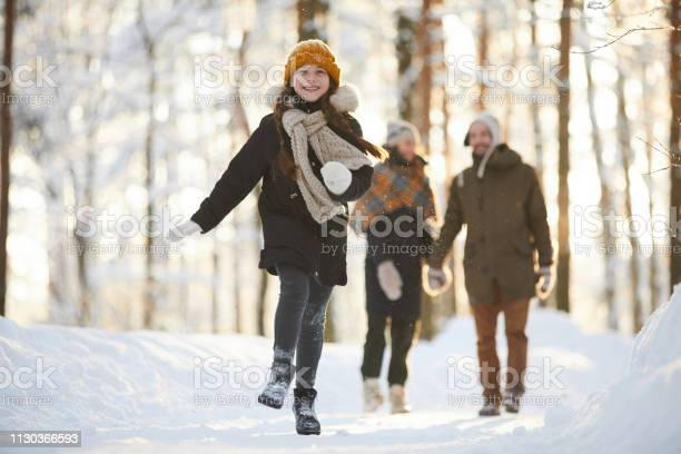 Photo of Happy Girl Running in Winter Forest