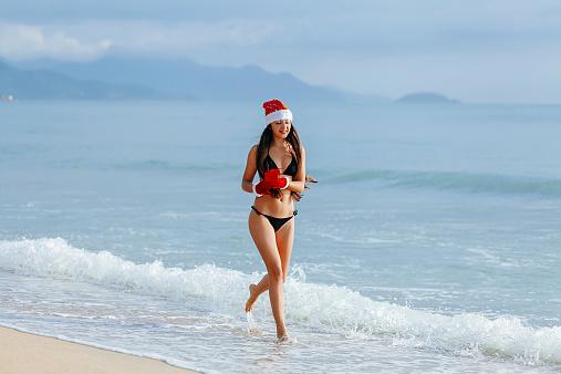 1155046257 istock photo happy girl running with chrismas gift on the beach 527796187