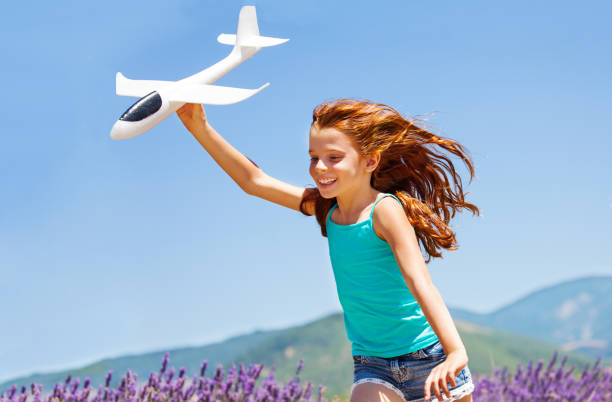 Happy girl running with toy plane outdoors stock photo