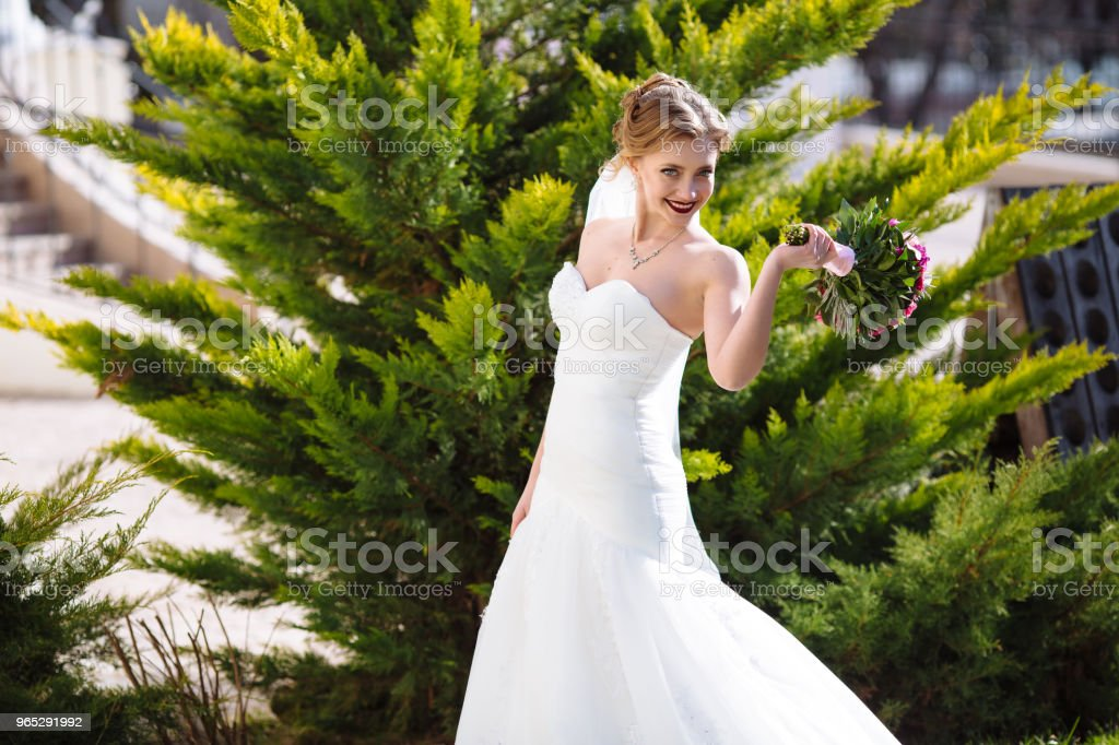 A happy girl runs around and plays in the garden amidst the greenery, smiling and enjoying the beauty of nature and her wedding royalty-free stock photo